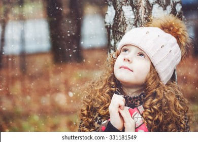 Praying little girl looking up with hope for peace. Happy childhood and world peace concept.
