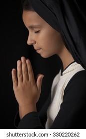 Praying little girl on black background