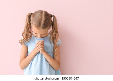 Praying little girl on color background