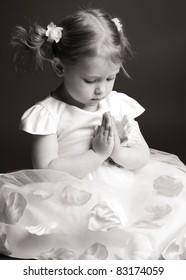 Praying little girl on gray background
