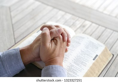 Praying: male hands clasped together on an old bible