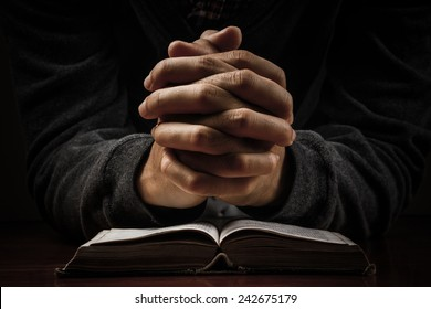 Praying man hands and bible on desk.