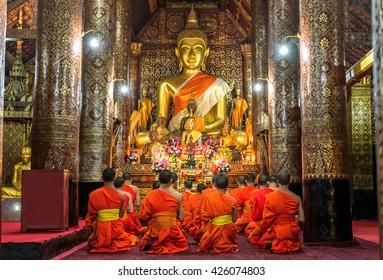 Praying Monks at Wat Xieng Thong luang prabang Laos.