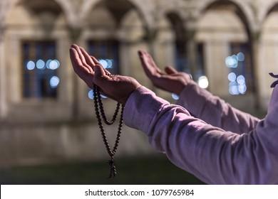 Praying Muslim Man with prayer-beads (Tesbih). Praying Muslim Man with mosque background in Ramadan Kareem. Istanbul, Turkey.