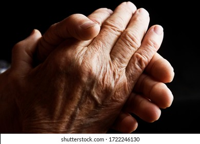 Praying old grandmother's hands close-up. Praying old grandmother in the dark about her children and grandchildren. Old wrinkled hands in prayer close-up. Aged hands asking for help.