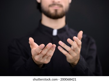 Praying priest. Portrait of priest standing isolated on black