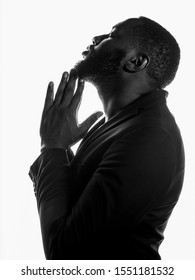 Praying profile side silhouette of African American bearded man in suit on white isolate background.