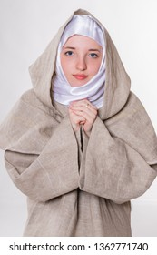 Praying pure girl in monastic clothes and white scarf