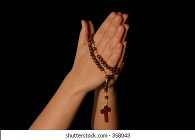 praying with a rosary, background is deep black