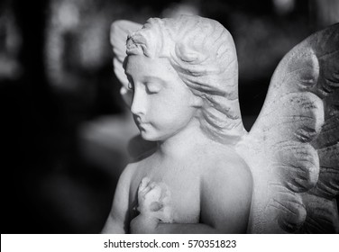 Praying statue of an angle looks down on a grave in a London cemetery