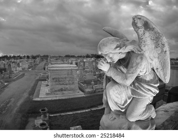 A praying statue kneels on top of a tomb in New Orleans under moody skies.  High point of view to contain the cemetery landscape in the background.