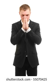 Praying young businessman. Isolated over white.