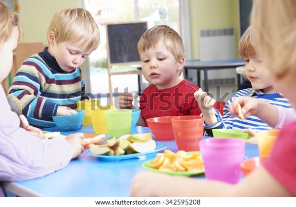 Pre School Children Eating Healthy Snacks At Breaktime