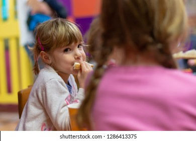 Pre school girl eating sandwich at birthday party