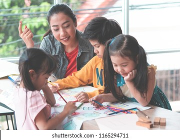 Pre School Small Student kids are painting on paper in Art group with teacher guiding them in Daycare school educational creativity concept.