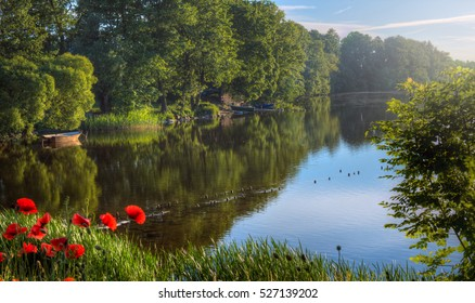 Pre sunset photo of lakeside landscape with lush trees, red poppy flowers and boats on the shore. Taken in the Mazury region of Poland.