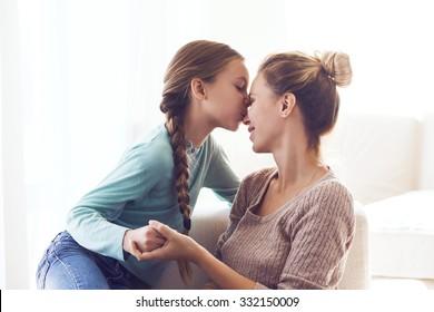 Pre teen daughter kissing her mom, positive feelings, good relations.