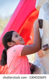 Pre teen girl with a strong arm is holding on to a grip on a rock climbing wall.