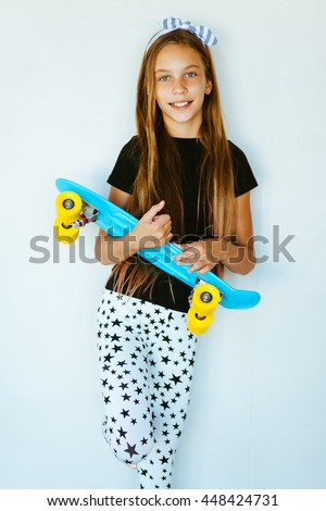 44810914a6bd Pre teen girl wearing cool fashion clothing posing with colorful skateboard  against white wall