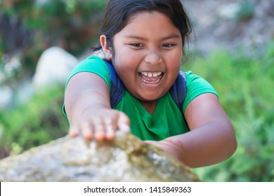 Pre teen student with backpack blocking a water fountain with her hands and having a great time playing after school.