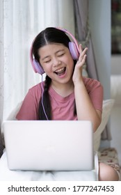 Pre Teen Studying on Devices, Stay at Home Stay Safe - front on purple headphones singing eyes closed hand on ear dancing movement looking at screen