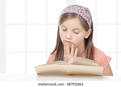 a pre teenage girl reads a book