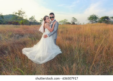 Pre wedding photos of bride and groom asian in concept love of family and fashion,Brown meadow and light sunshine.