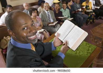 Preacher Holding Bible in Front of Congregation
