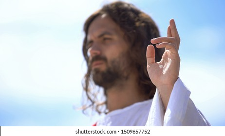 Preacher showing blessing sign against blue sky, hand of benediction, baptism