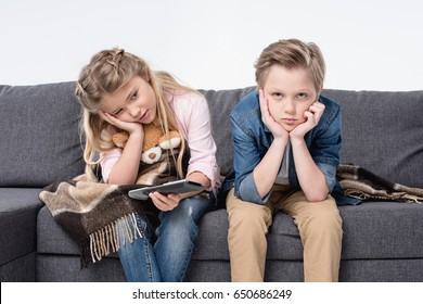 pre-adolescent bored brother and sister sitting on sofa and holding remote control
