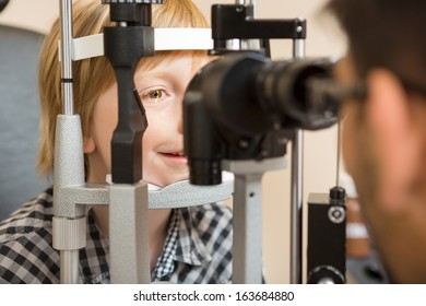 Preadolescent boy's eyes being examined by slit lamp in store