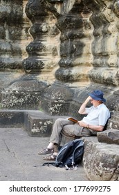 Preah Vihear Temple,Cambodia-Oct 21,2012 :Unidentified tourist sit on stone reading guide book on October 21,2012 in Preah Vihear Temple Cambodia.