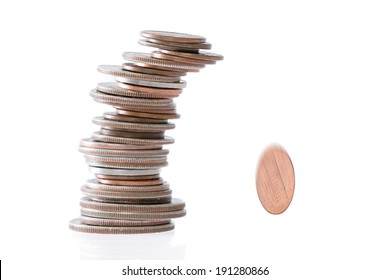 Precarious stack of coins of different denominations leaning to the side and falling over with one coin rolling away with motion blur on a white background with copy space in a conceptual image