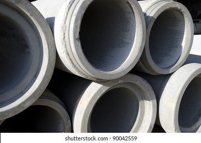 Precast concrete pipe is stacked on a construction job site