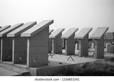 Precast concrete shapes in a lay down area are awaiting incorporation into a new construction project. (Monochrome image.)
