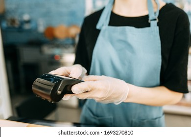 Precautions during quarantine. A gloved waiter with a cashless payment terminal.