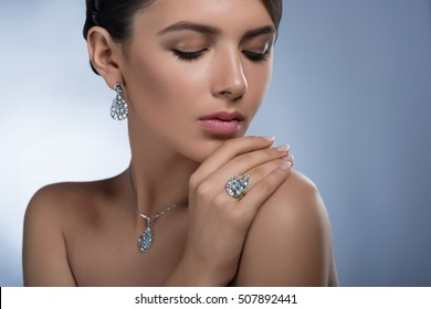 Precious accessories. Closeup studio portrait of a gorgeous young elegant female wearing diamond earrings ring and necklace posing with her eyes closed