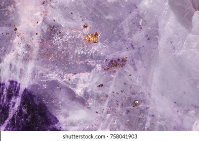 Precious metal gold as inclusions in the crystal of amethyst quartz. Close-up of raw unpolished crystal of amethyst quartz. Natural mineral stone texture and surface background.