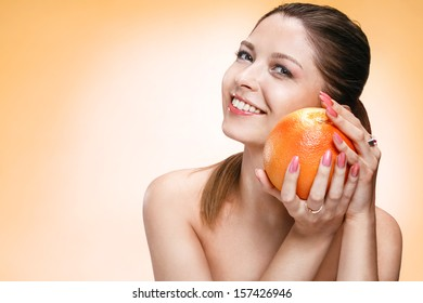 Precious woman with orange fruit / studio photo of brown-eyed brunette girl holding an orange and smiling - isolated on orange background