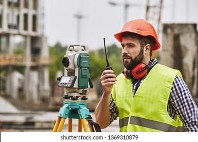 Precise measurements. Surveyor engineer in protective wear and red helmet using geodetic equipment and talking by walkie talkie while standing at construction site. Professional equipment.