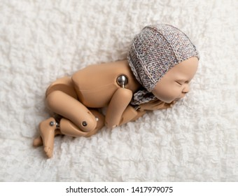 Precisely accurate mannequin of newborn in a hat for photo practicing