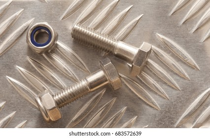 Precision Engineering Concept, Close-up view of two nut bolts over shiny anti-slip stainless steel metal surface