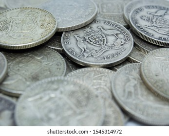 Pre-decimal Australian Sterling silver coins in a pile with both the old and new Australian Coat of Arms. Known as a Florin or Two Shilling and Two Bob these coins are 92.5% silver and 7.5% copper.