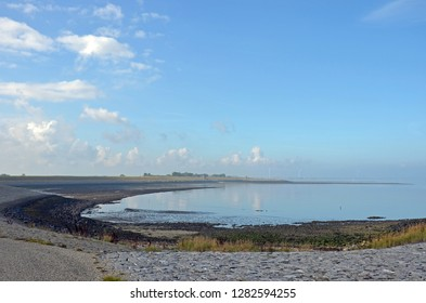 A predominantly blue sky with some scattered clouds over the sandy north coast of the island of Noord-Beveland, The Netherlands and Oosterschelde estuary