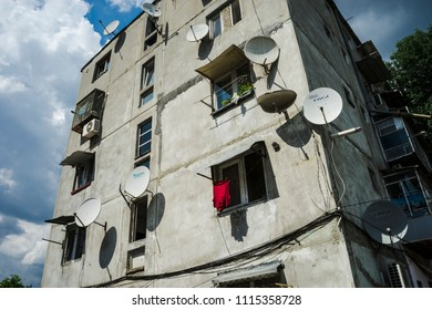 Prefab and dishes antennas/Socialist style architecture prefabricated building with lots of antenna dishes and laundry at the window. Bucharest, Romania, May 5, 2018.