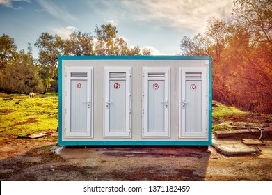 Prefabricated portable cabin with four numbered doors on a meadow field in the forest