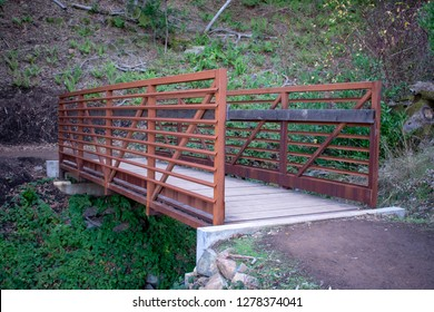 Prefabricated small steel bridge on hiking trail over dry creek in park with green background