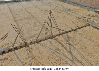 Prefabrication hollow core concrete plank close up with reinforced post tension steel floor structure in orange day flare light and shadow, use for background cover material and texture.