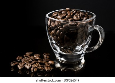 I prefer my coffee black. Espresso coffee beans in a glass cup standing on a mirror, with beans also on the side, isolated on black background.