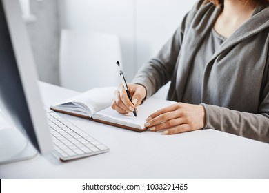 I prefer old-school writing method. Cropped portrait of busy woman making notes in notebook, looking at computer screen during work-time in office, trying to concentrate and focus on assignment